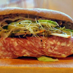 Sandwich med Fennikelpølse, gedeost, cornichon, salat og pesto