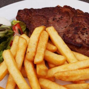 Steak med pommes frites samt sauce/dip, salat og dressing